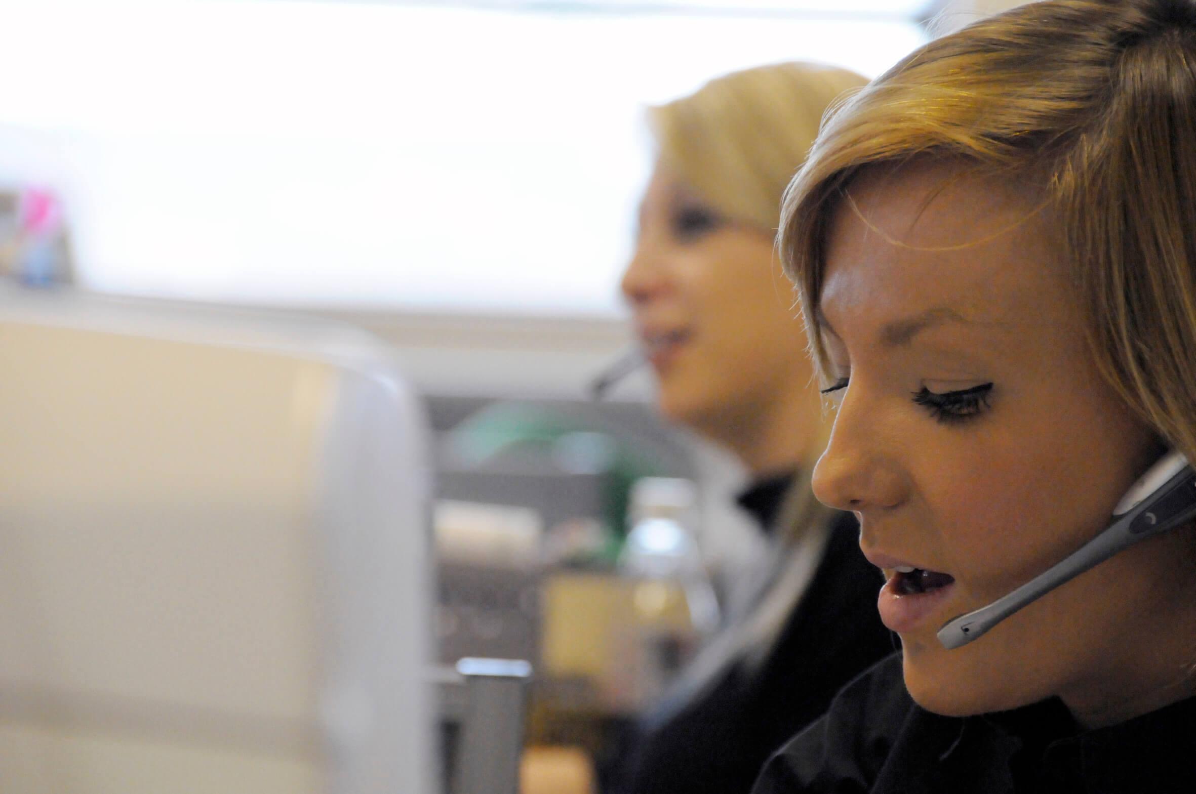 Two businesswomen talking on headsets