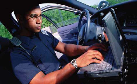 Police officer using a laptop in his vehicle