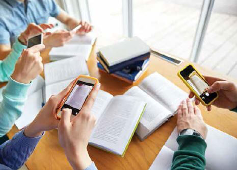 Four people taking iPhone photos of open books