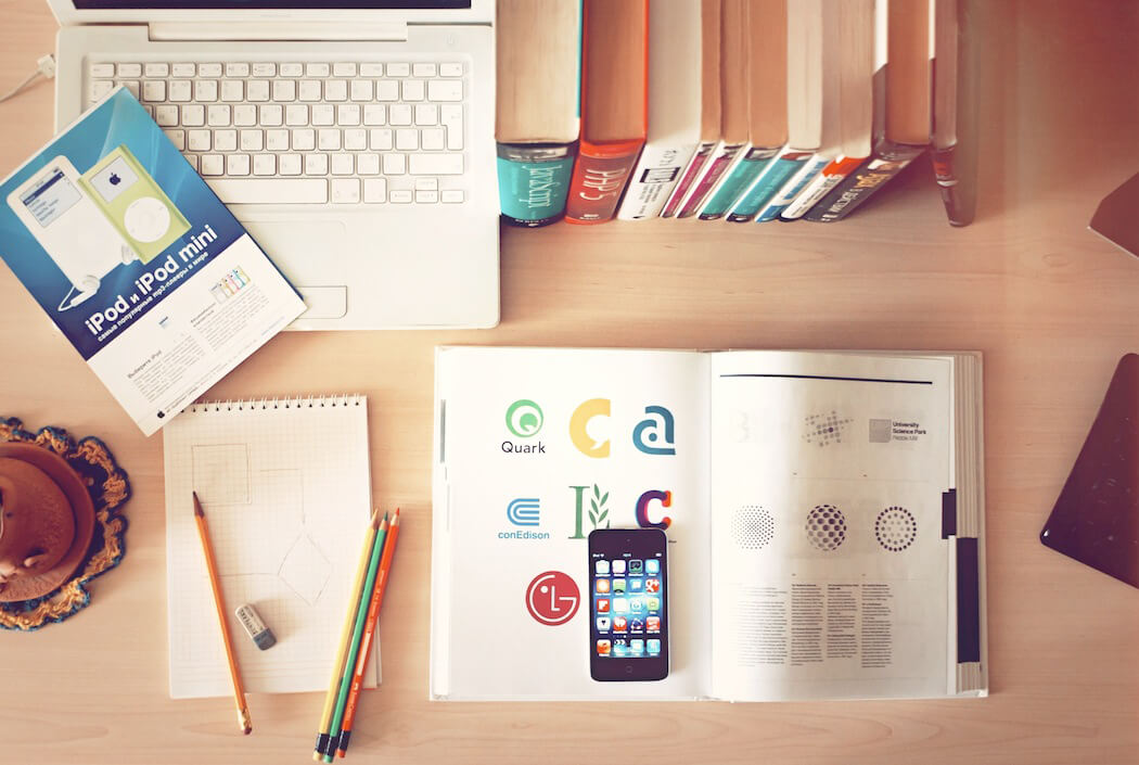 Books, a notebook, and Apple products on a desk