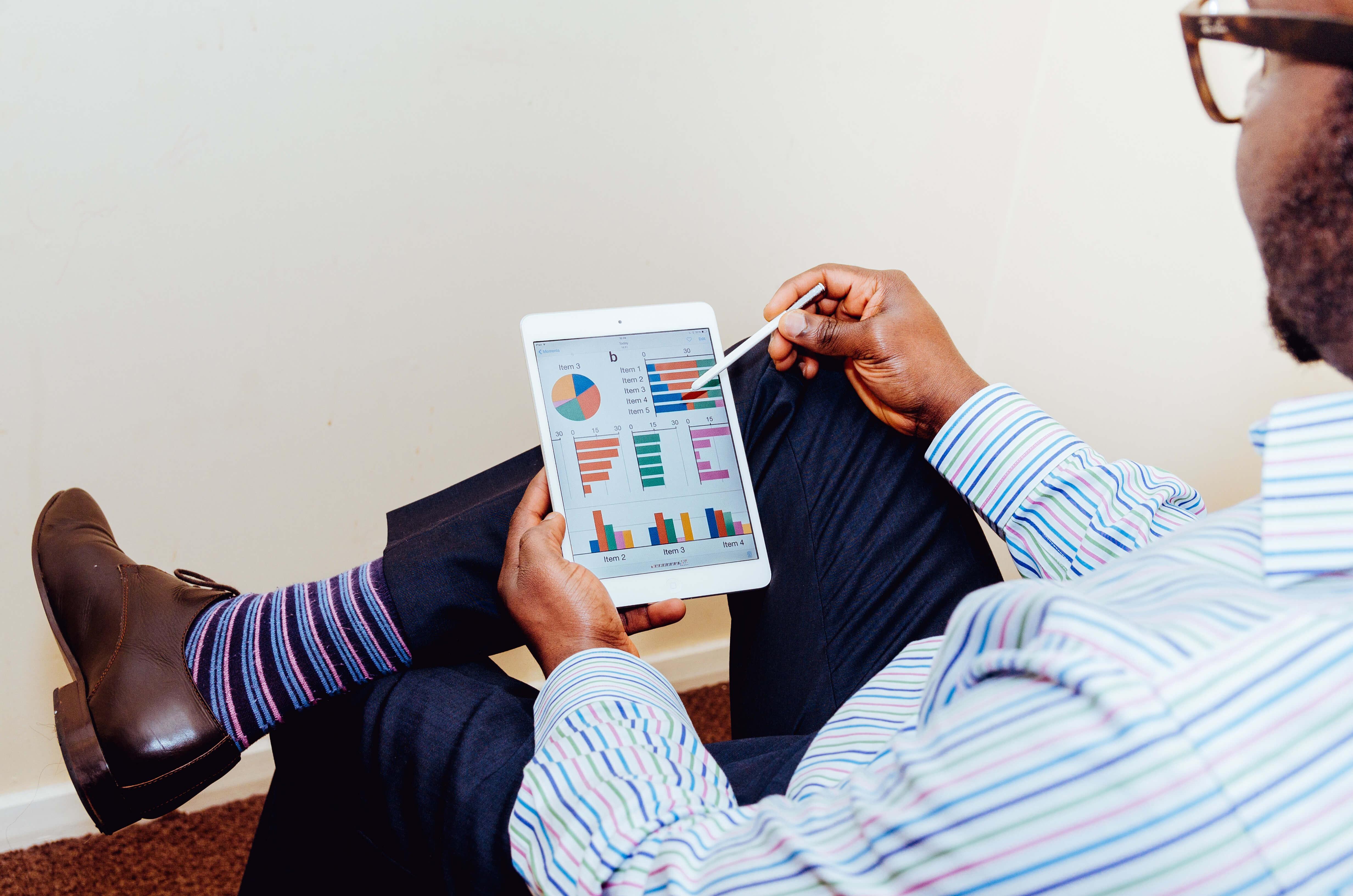 Man looking at charts via a tablet