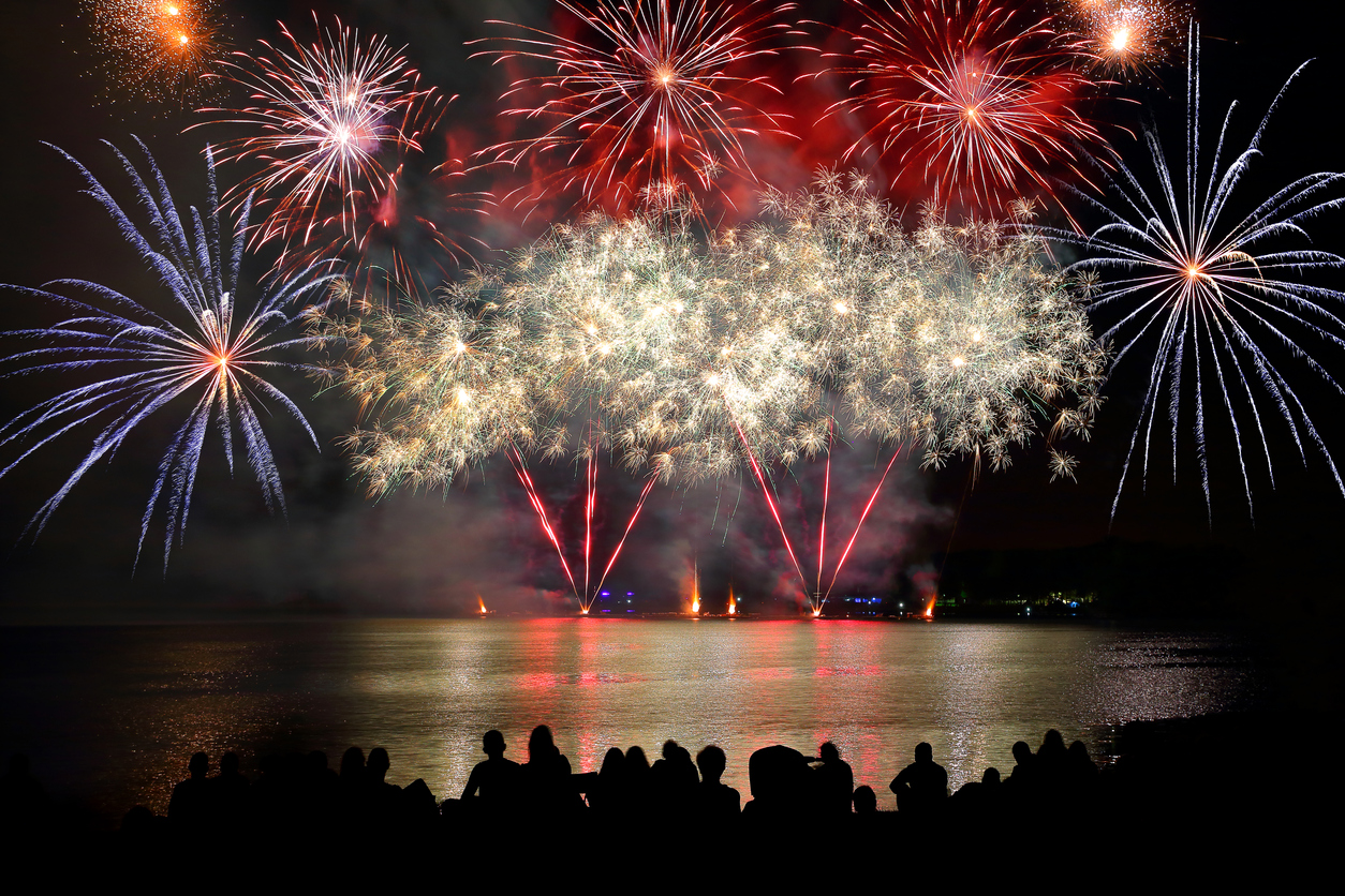 Crowd watching a firework display over a body of water