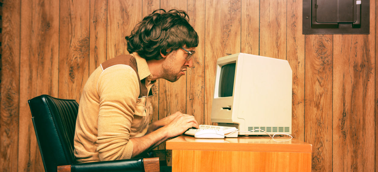 Satirical image of man working at a computer in the 1970s