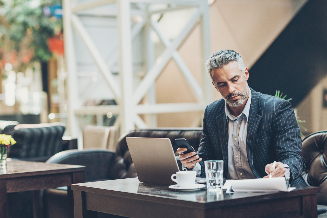 Man working from a laptop, phone, and notebook