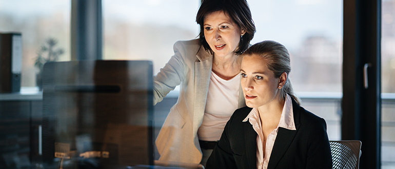Two businesswomen looking at a computer screen